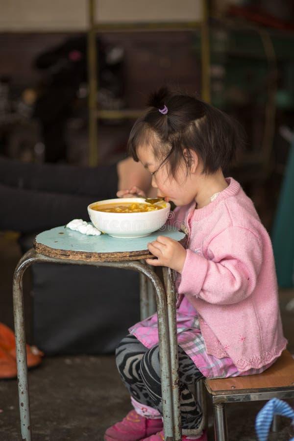 吃在一张蓝色桌上的女孩在上海 库存照片