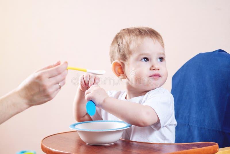 吃在一把椅子的可爱宝贝男孩在厨房里 妈妈哺养在手中拿着粥匙子  免版税库存照片
