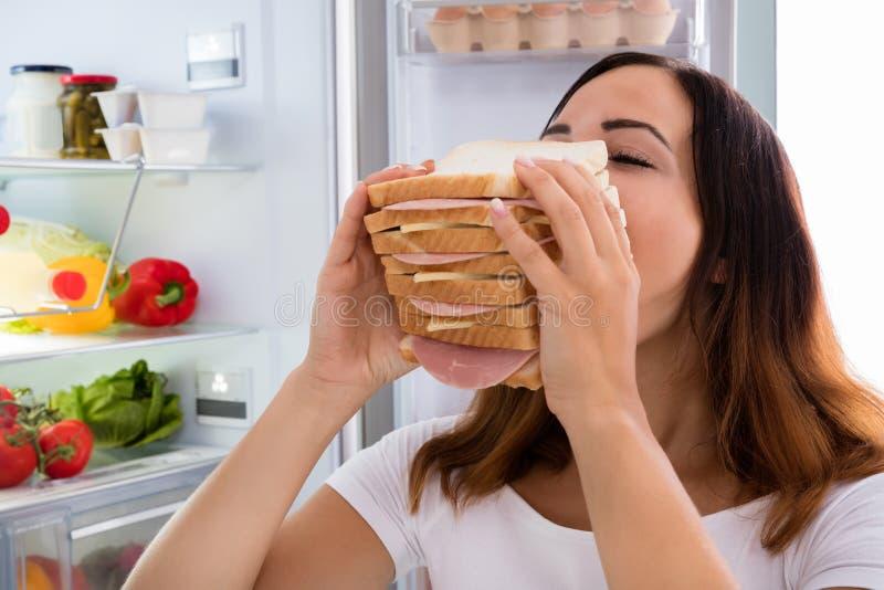 吃在冰箱前面的妇女三明治 免版税图库摄影