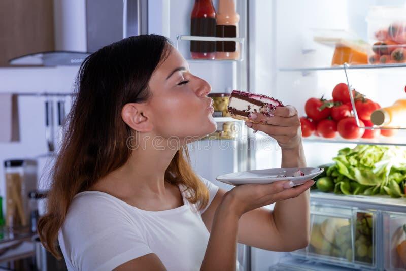 吃在冰箱前面的妇女蛋糕 免版税图库摄影