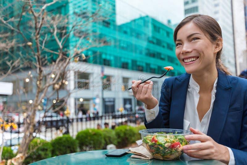 吃在午休的女商人沙拉在城市公园 库存照片