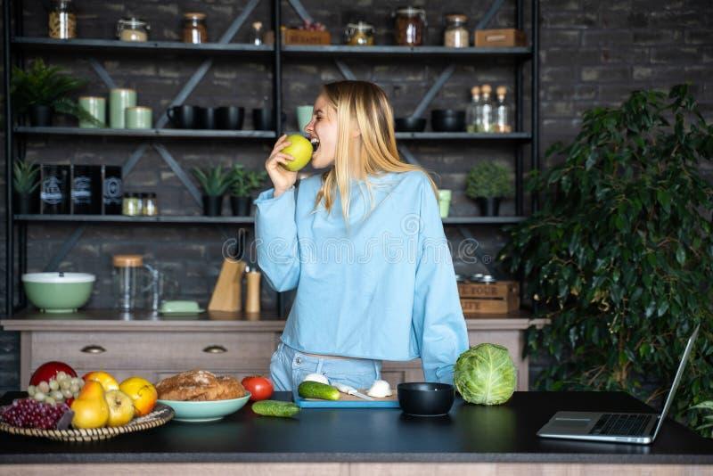 吃在厨房的愉快的年轻女人绿色苹果计算机 免版税库存照片