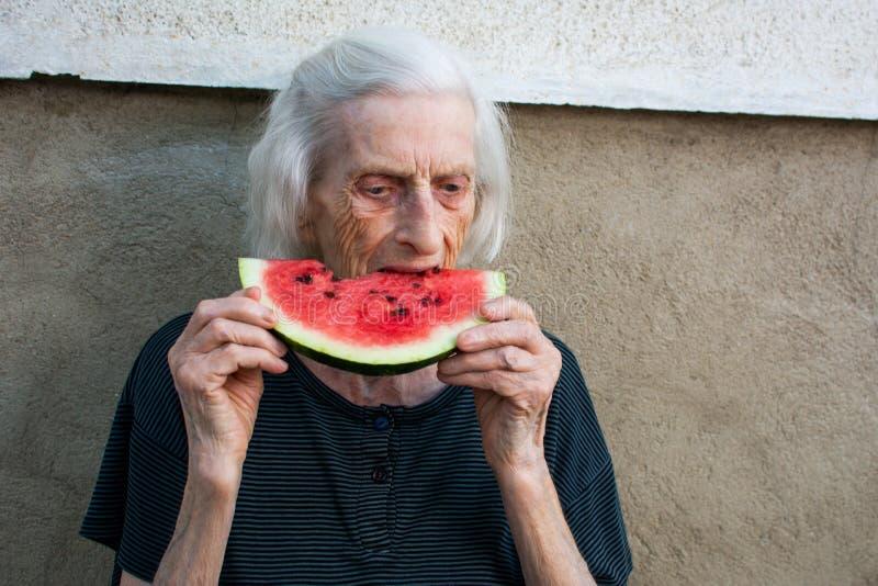吃西瓜的资深妇女户外 免版税库存照片