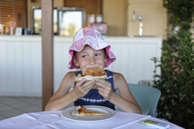 吃在咖啡馆的女孩比萨 免版税库存照片
