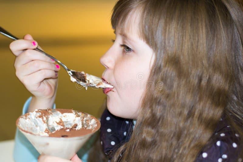 吃在咖啡馆的小女孩冰淇凌 免版税库存图片