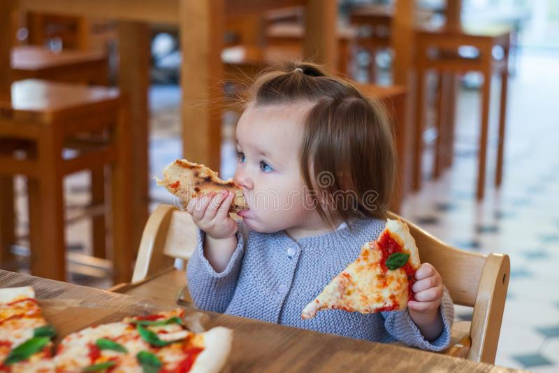 吃在咖啡馆的逗人喜爱的矮小的小孩女孩薄饼 库存照片