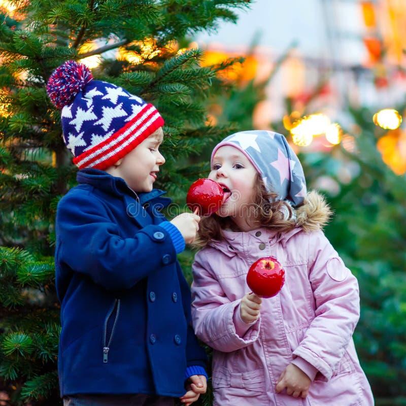 吃在圣诞节市场上的两个小孩被结晶的苹果 免版税库存图片