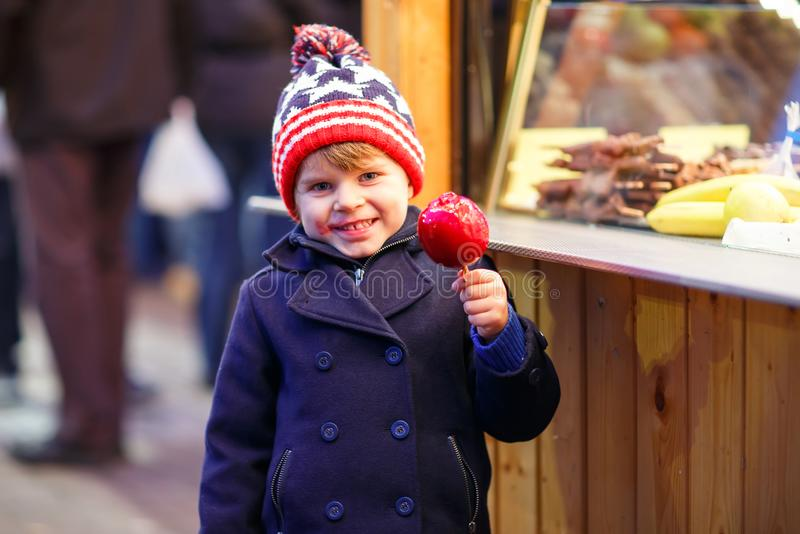 吃在圣诞节市场上的小孩男孩甜苹果 免版税库存图片