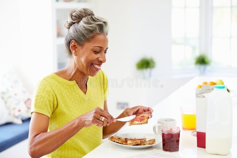 吃在多士的成熟妇女早餐传播的果酱 免版税库存图片