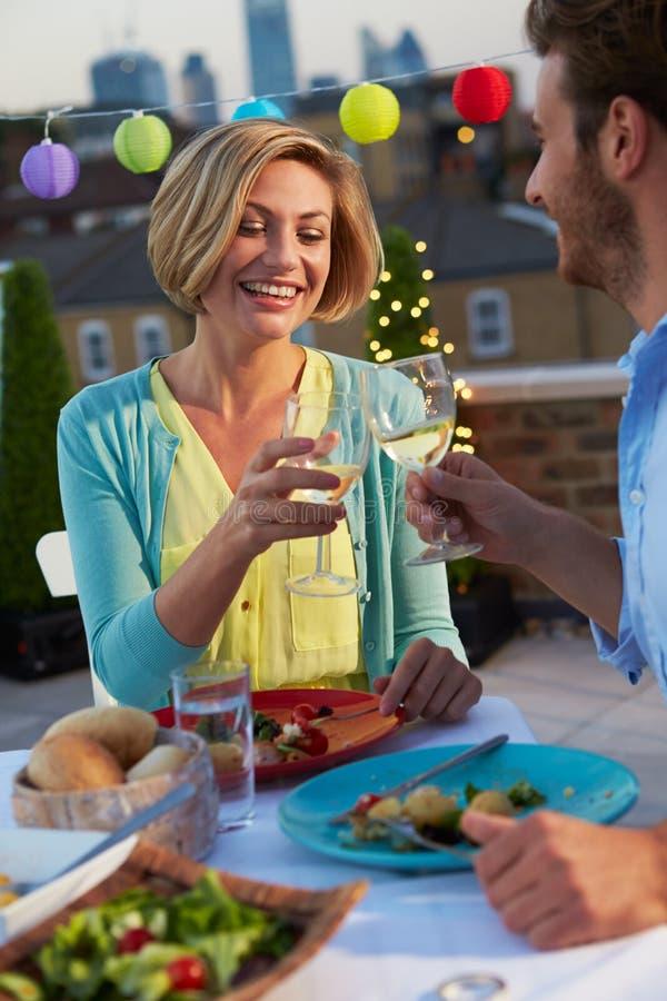 吃在屋顶大阳台的夫妇晚餐 免版税图库摄影