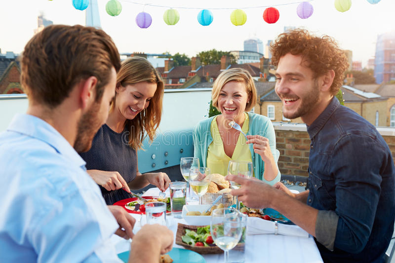 吃在屋顶大阳台的小组朋友膳食 图库摄影