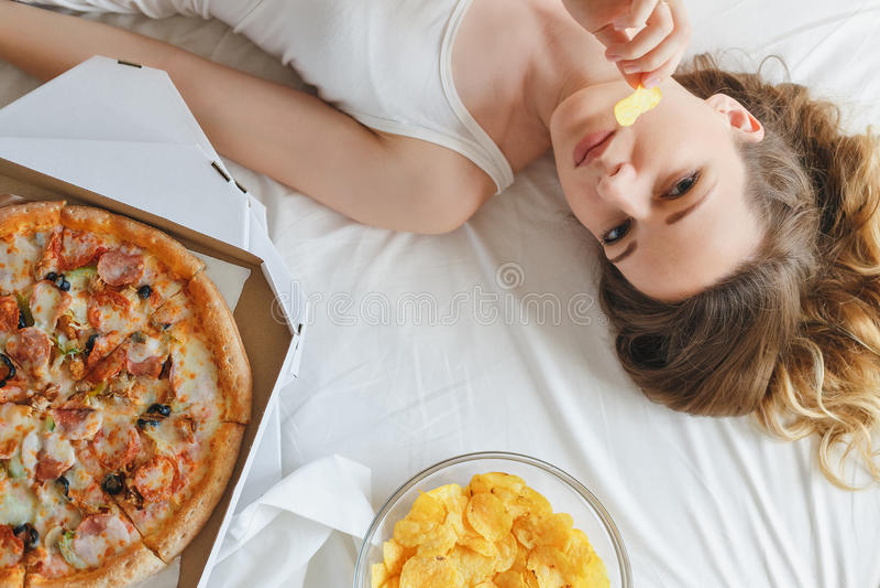 吃在床上的女孩芯片,站立在薄饼旁边 免版税图库摄影