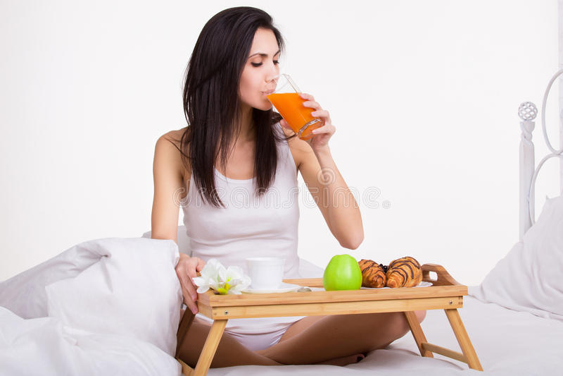 吃在床饮用的汁液的少妇早餐 库存图片