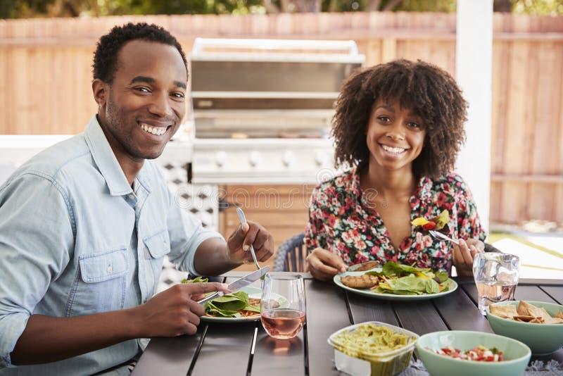 吃在庭院里的年轻黑夫妇看对照相机 库存图片
