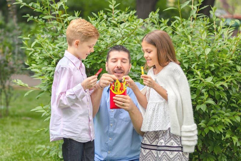 """吃在拿着五颜六色的胡椒的自然â€的微笑的父亲和孩子新鲜蔬菜""""愉快的爸爸切以薯条的形式 免版税库存照片"""