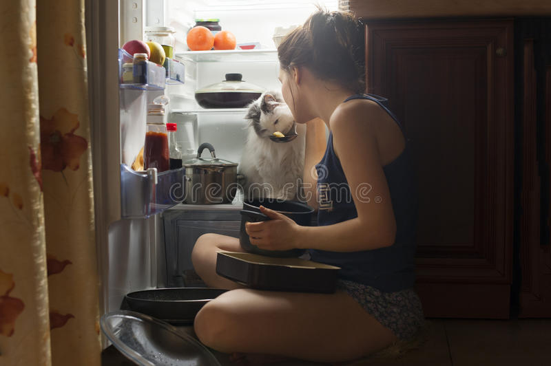 吃在晚上的女孩和她的蓬松猫 免版税图库摄影