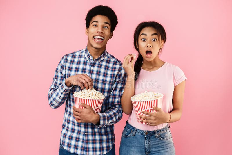 吃在桃红色背景的非裔美国人的夫妇玉米花 免版税库存照片