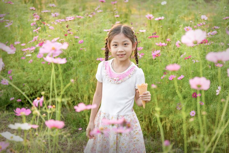 吃在桃红色花的领域的逗人喜爱的小女孩冰淇凌 图库摄影