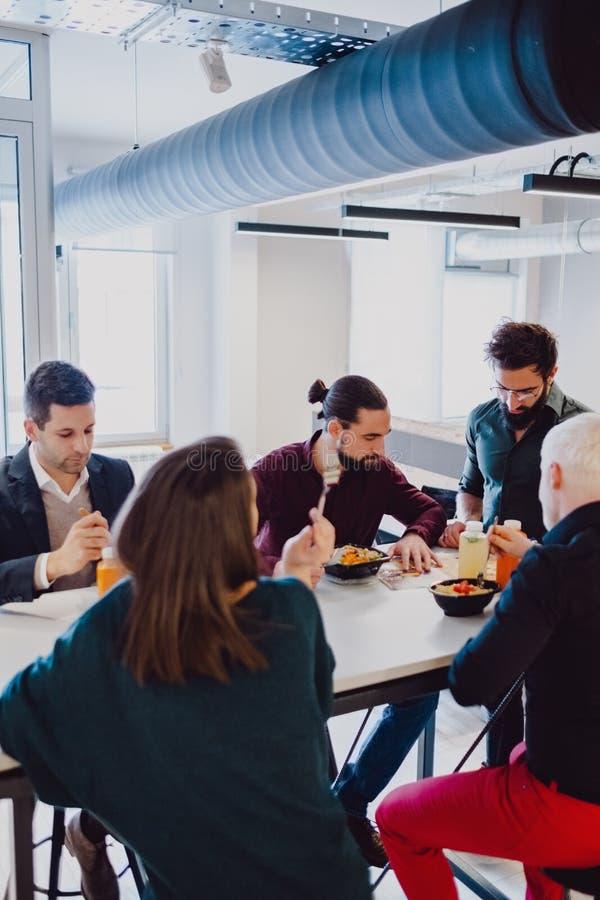 吃在桌上的严肃的工友在办公室 免版税图库摄影