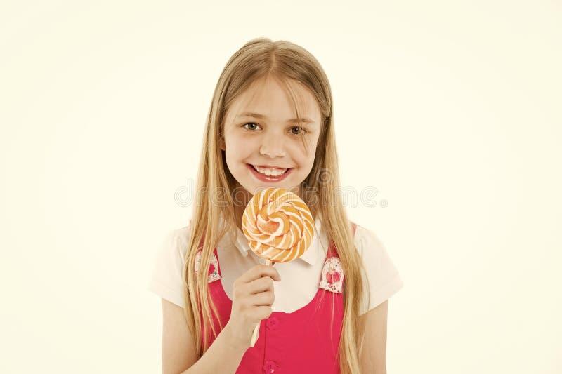 吃在棍子或棒棒糖的女孩大糖果 r 笑容的女孩拿着巨型五颜六色的棒棒糖  图库摄影