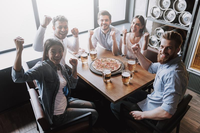 吃在比萨店的快乐的多种族朋友 库存照片