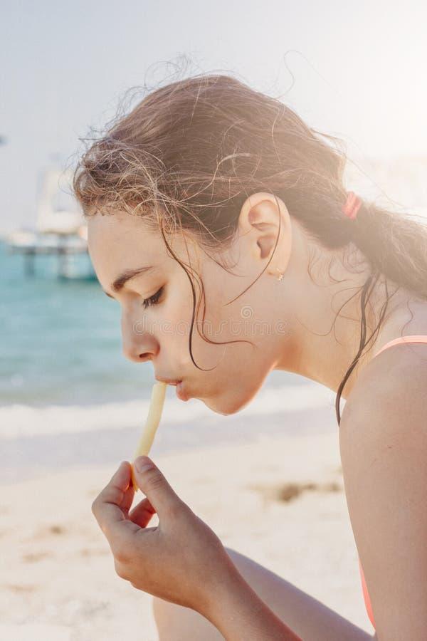 吃在海滩的年轻俏丽的少年女孩薯条在海附近 库存照片