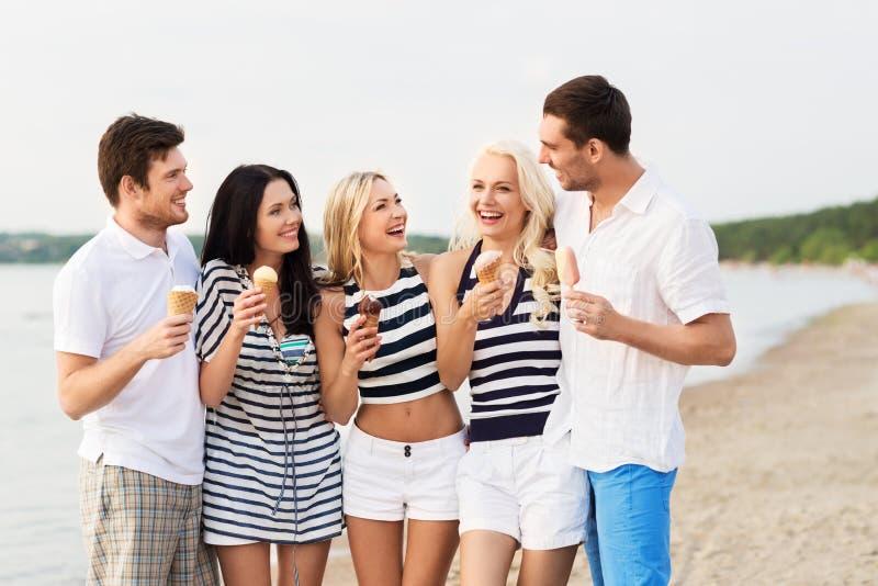 吃在海滩的愉快的朋友冰淇淋 免版税图库摄影