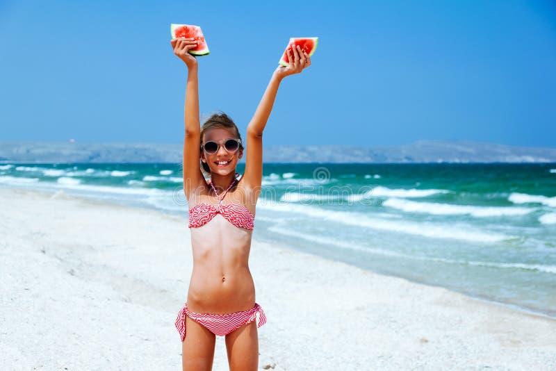 吃在海滩的孩子西瓜 免版税库存图片