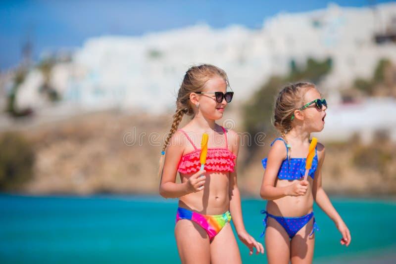 吃在海滩的愉快的小女孩冰淇凌 库存照片