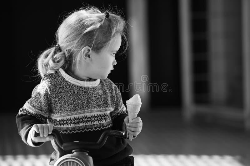 吃在玩具自行车的婴孩或小男孩冰淇凌 免版税库存照片