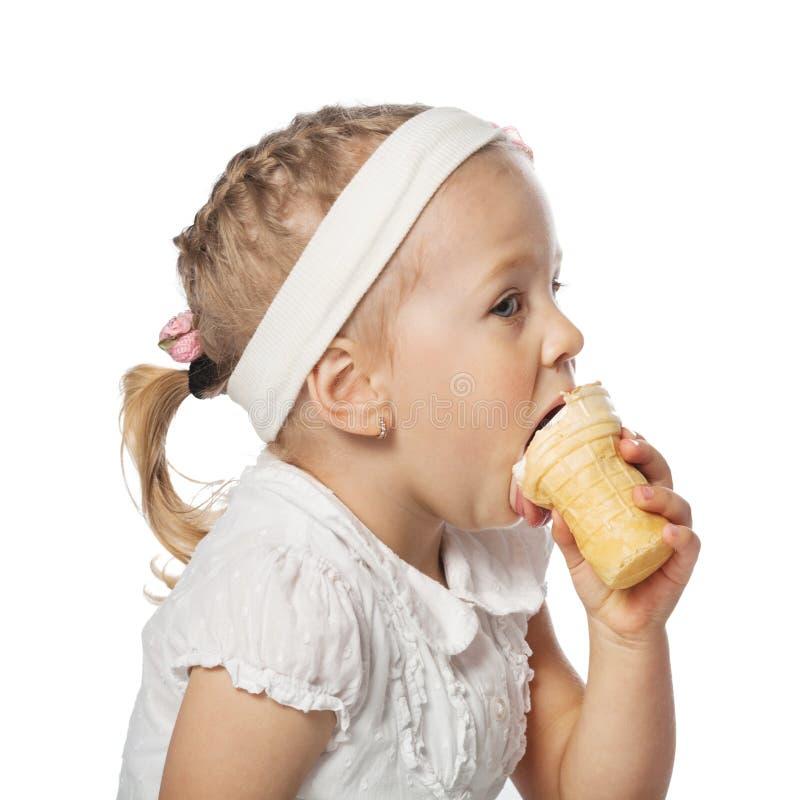 吃在白色的小女孩冰淇凌 免版税库存图片