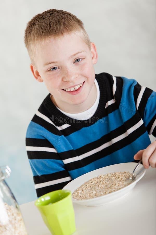 吃在碗的愉快的白肤金发的孩子燕麦粥在桌上 免版税库存照片