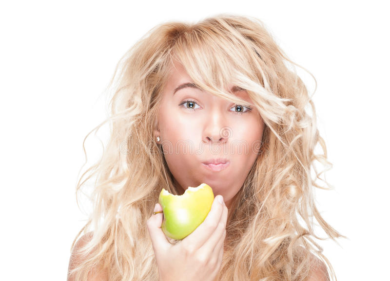 吃在空白背景的女孩绿色苹果。 免版税库存照片