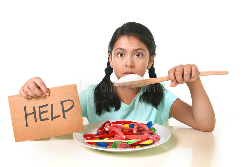 吃在糖果盘的小孩甜糖举行糖spoo 库存图片