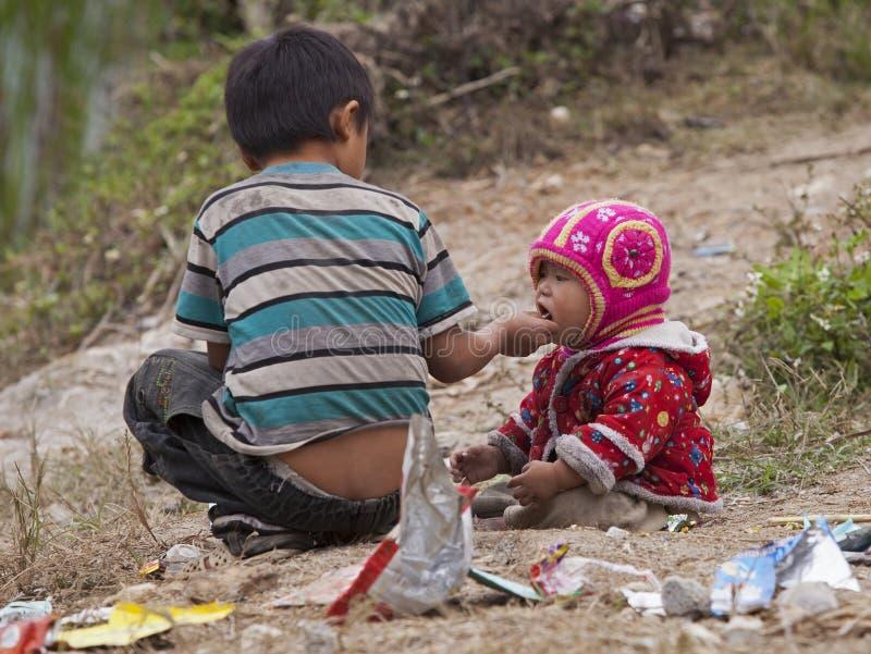 吃在肮脏的地面上的Hmong孩子糖果在东范岩石高原 免版税库存照片