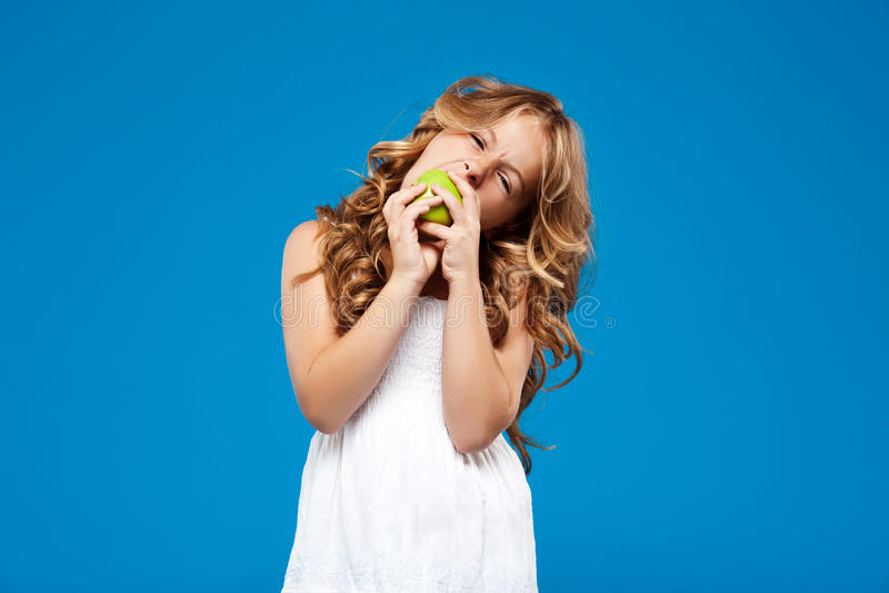 吃在蓝色背景的年轻俏丽的女孩绿色苹果 库存图片