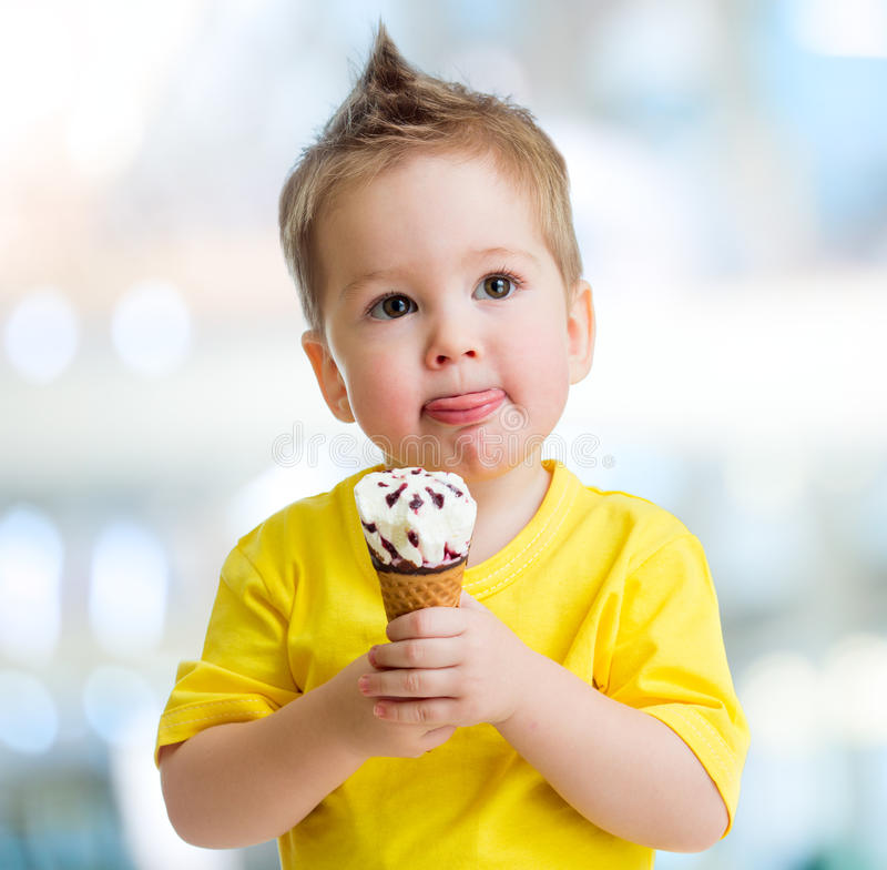 吃在被弄脏的背景的滑稽的孩子冰淇凌 库存照片