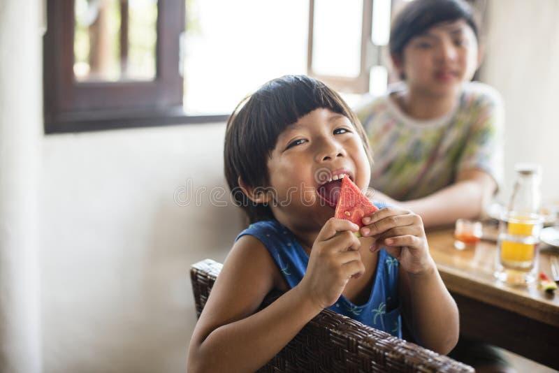 吃在西瓜的亚裔男孩 免版税库存照片