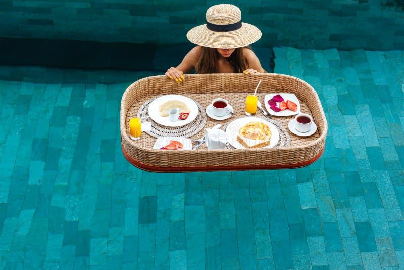 吃在豪华旅馆水池的女孩浮动早餐 免版税图库摄影