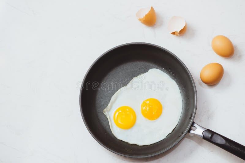 吃在过程中,在一个煎锅的煎蛋在白色背景的早餐 白天 免版税图库摄影