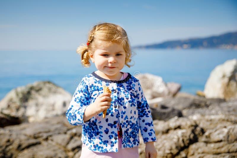 吃在锥体的逗人喜爱的矮小的小孩女孩冰淇淋家庭度假 愉快的健康小孩子用冰淇凌奶蛋烘饼 免版税库存照片