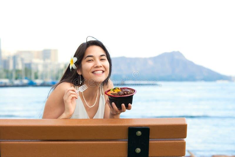 吃在长凳的少妇夏威夷bqq牛肉在夏威夷 免版税库存图片