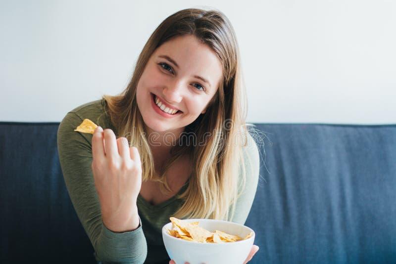 吃在长沙发的年轻女人快餐 免版税库存照片