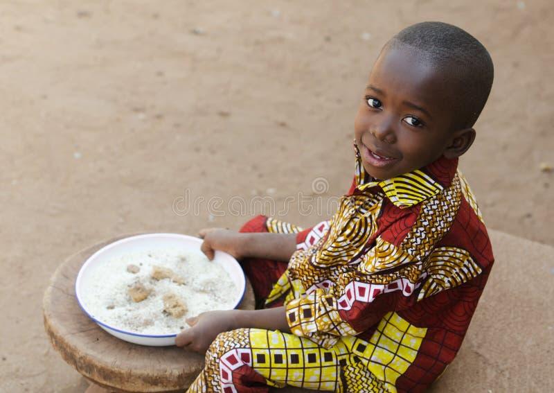 吃在非洲-小的黑男孩饥饿标志 免版税图库摄影