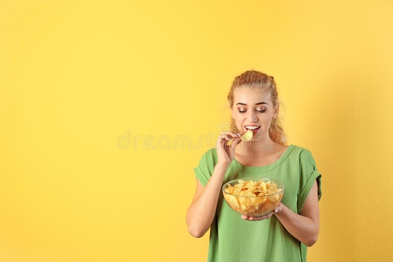 吃在颜色背景的妇女薯片 图库摄影