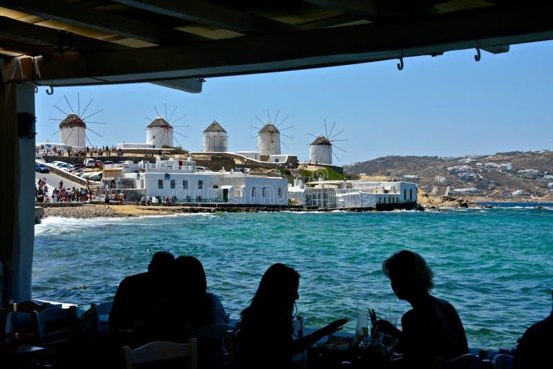 吃在餐馆海滨人行道和白色风车的游人剪影  图库摄影