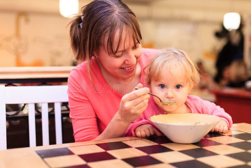 吃在餐馆的母亲和小婴孩 免版税库存照片