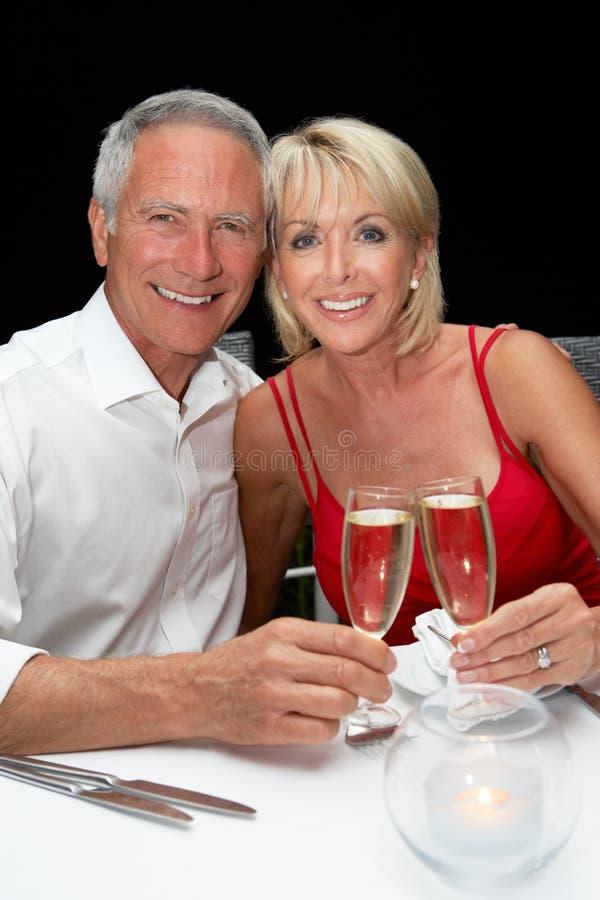 吃在餐馆的高级夫妇 免版税库存图片