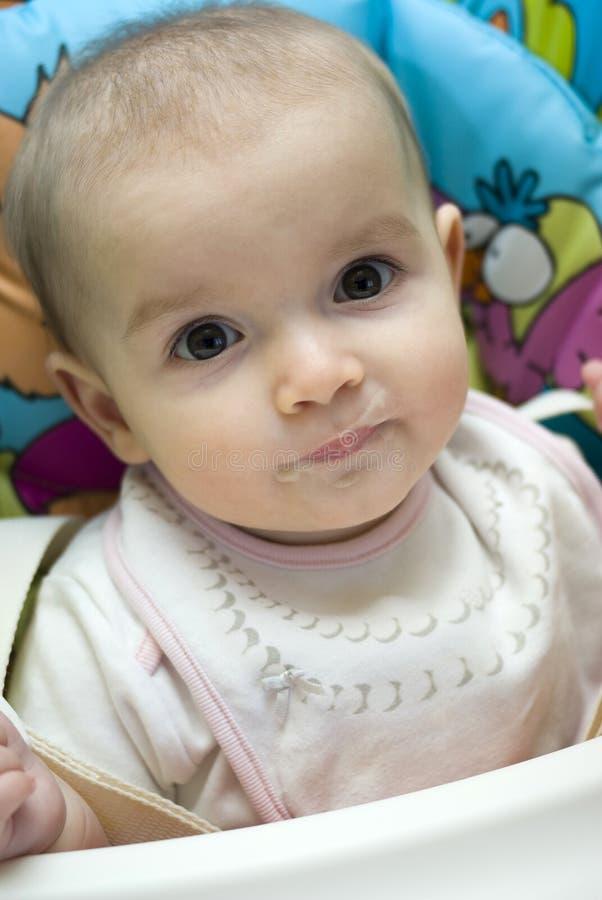 吃在高脚椅子的女婴 免版税库存照片