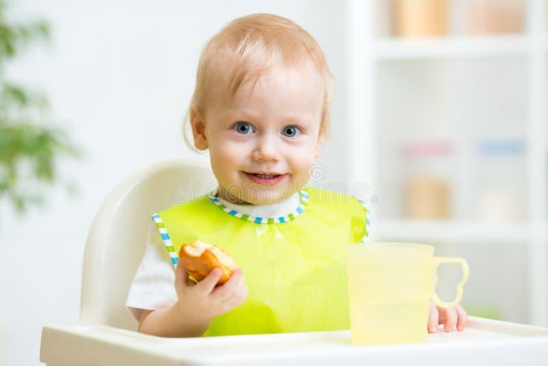 吃在高脚椅子的孩子食物 免版税库存照片
